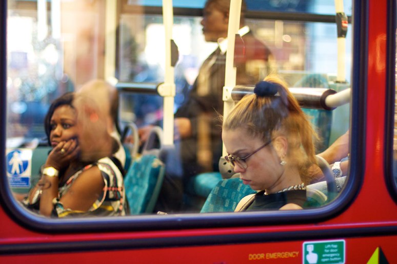Young woman reads a book on a bus
