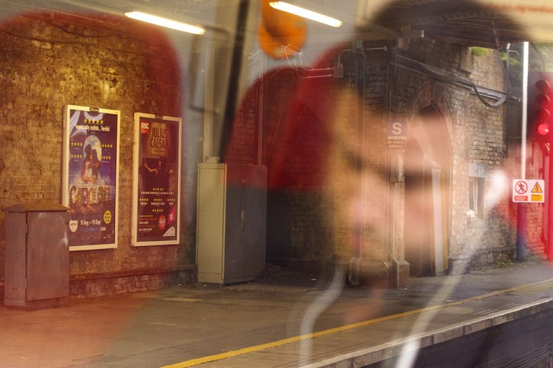 Man with earphones in, reflected in a train window