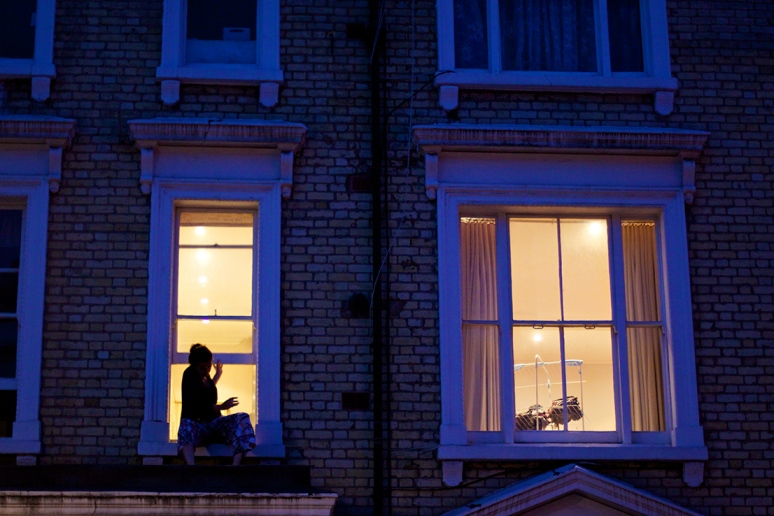 A woman sitting on a window ledge in a lit up window