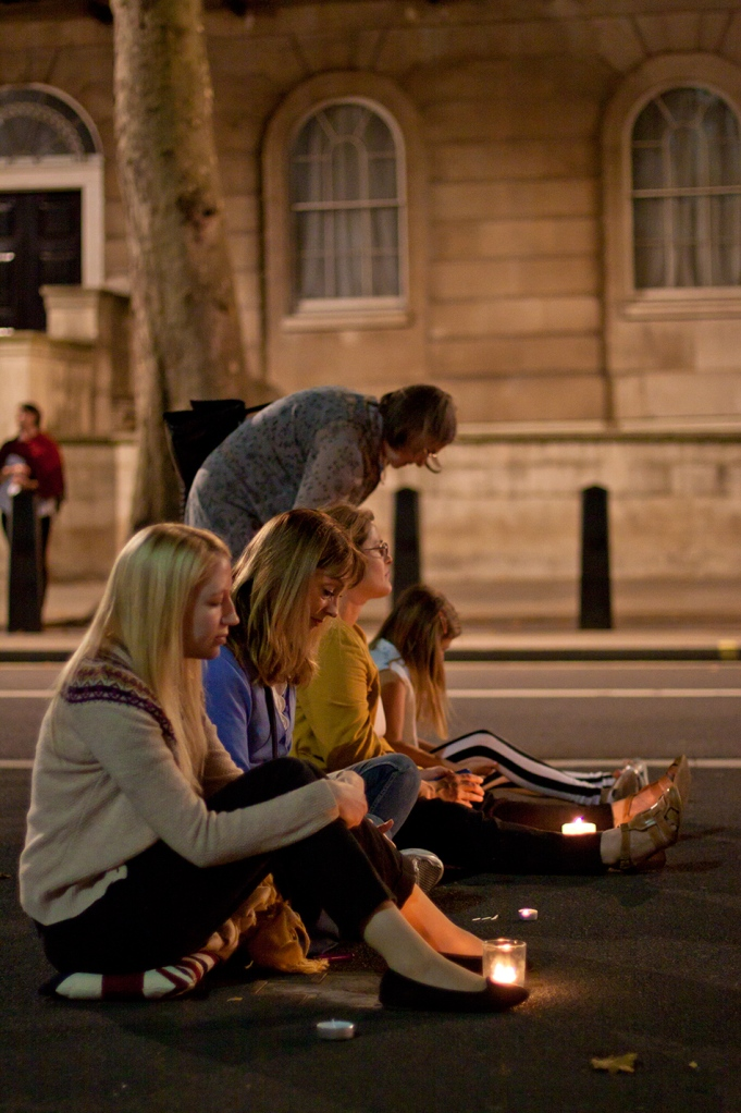 Women sit with candles at the Cenotaph in London