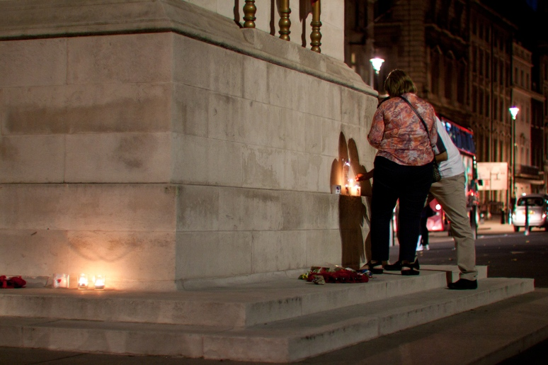 A man and a woman lighting candles at the Cenotaph