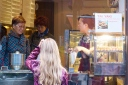 Girl with her hand to her head looks longingly into the window of cake shop in China Town where a woman is making cakes