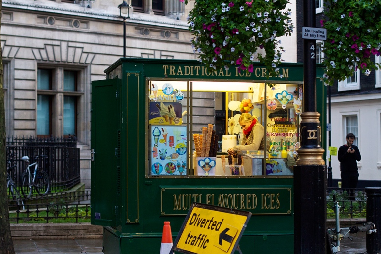 A woman sits alone in an ice cream kiosk in the West End of London