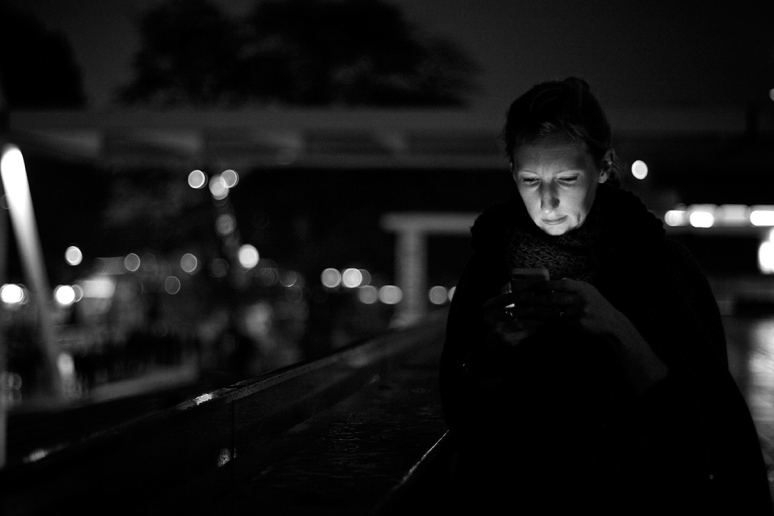 Woman's face lit by mobile phone
