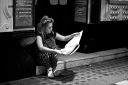 Young woman reading a newspaper, sitting on a step outside a theatre
