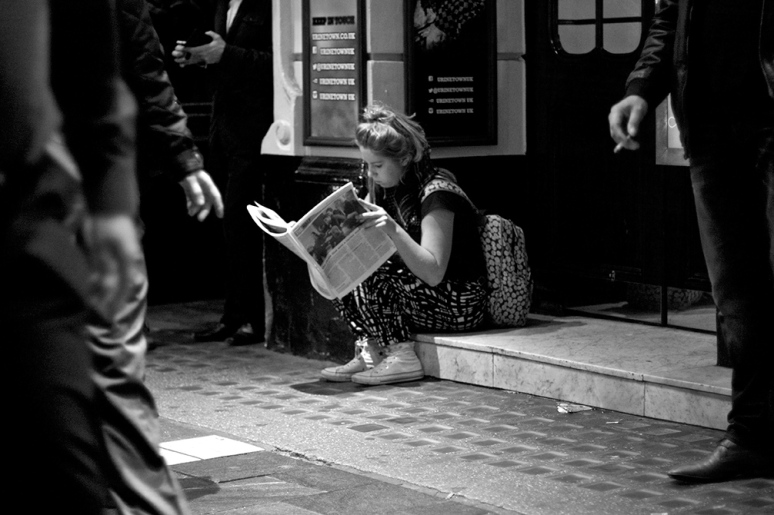 Young woman sitting on a step outside a theatre reading a newspaper