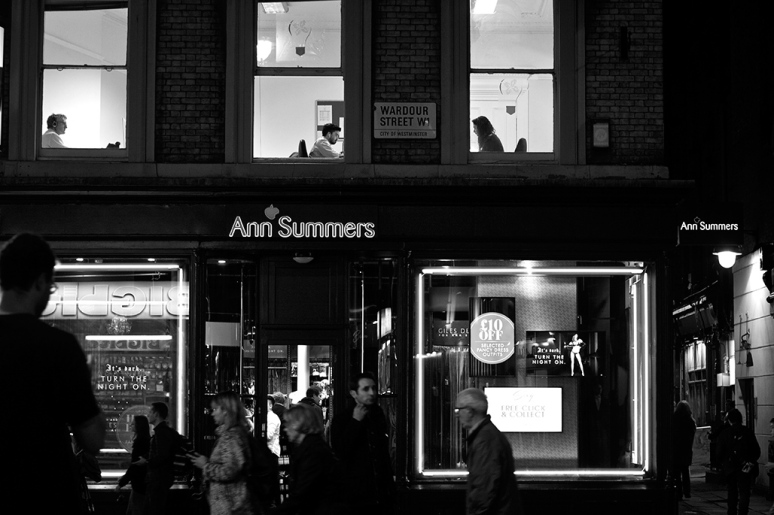 Three people working in an office above an Ann Summers shop in Soho