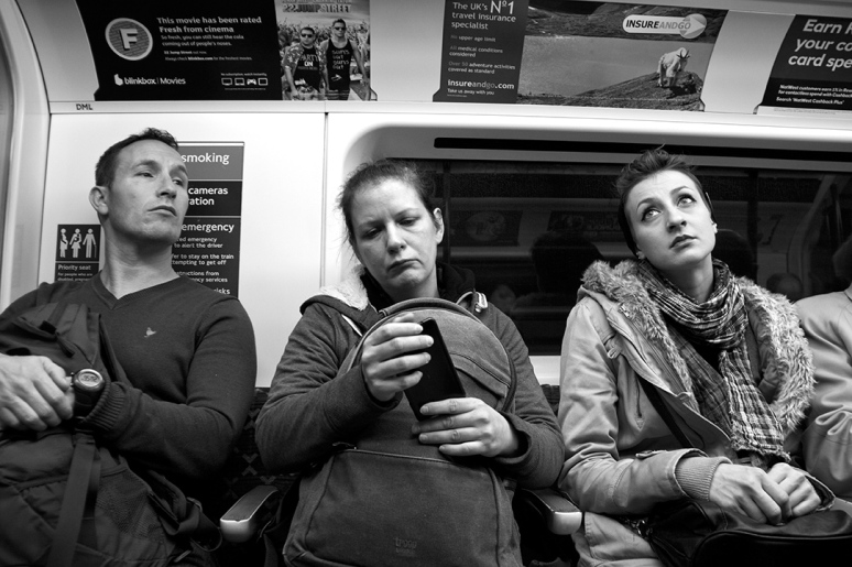 Two women and a man on the Tube in London, not speaking to each other