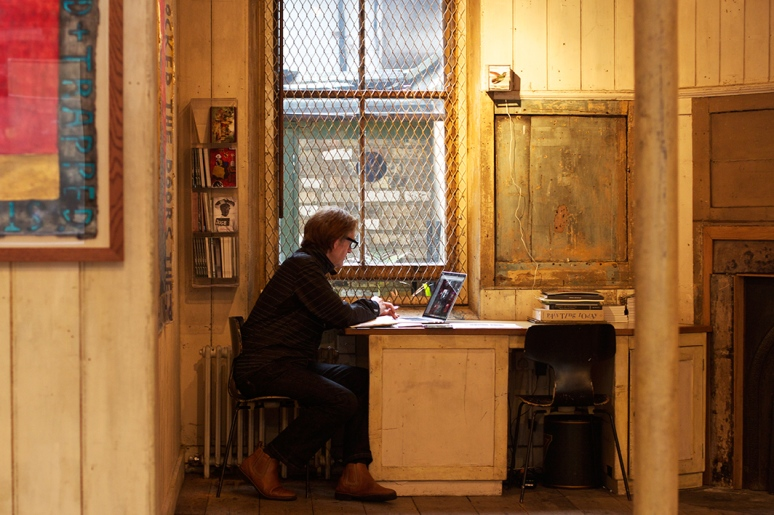 A man sits at his desk at an art gallery in Soho
