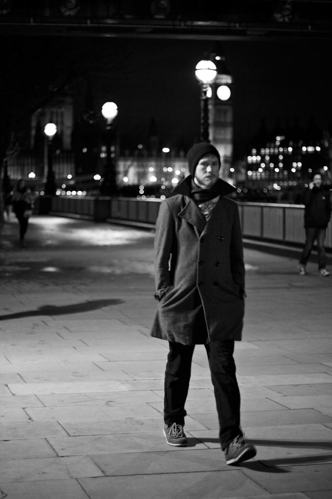 Young man walks alone on the South Bank in London with Big Ben in the background