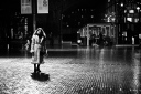 A woman walking alone across a wet square at night