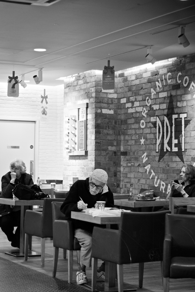 Three people on their own in a coffee shop, Pret a Manger, in Covent Garden
