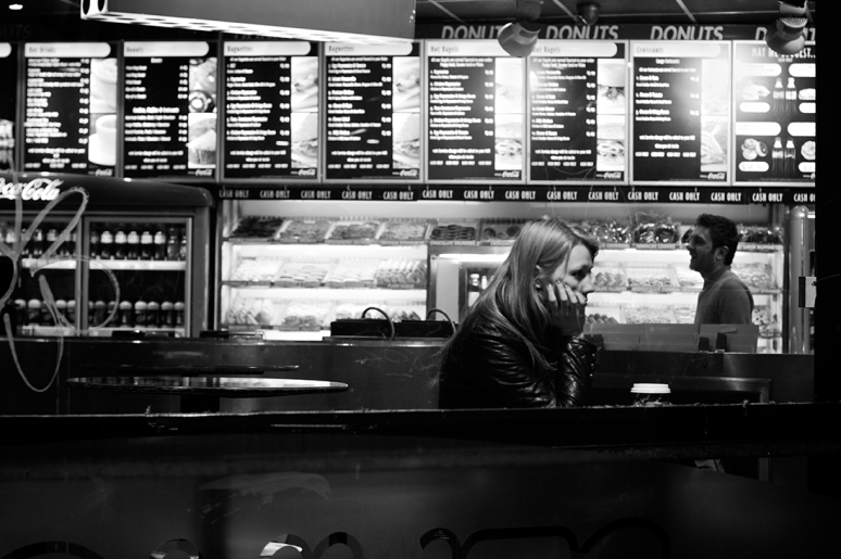 A young woman looking bored on her own in a London cafe at night