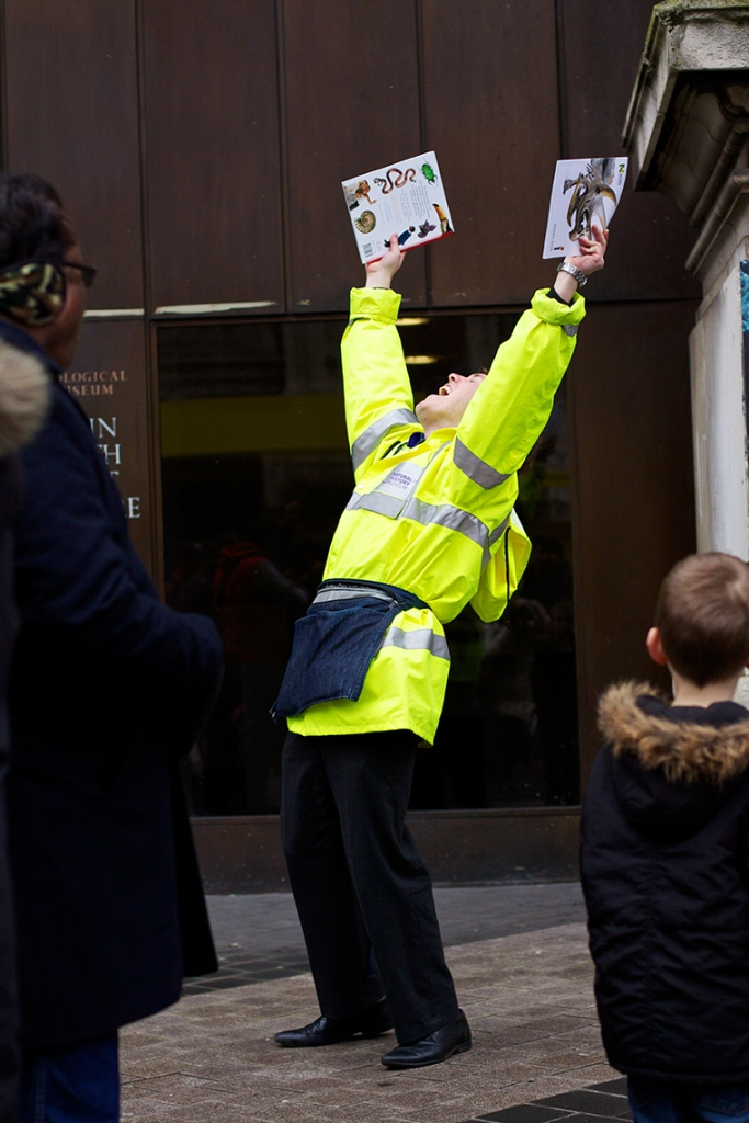 Man in high vis jacket with his arms above his head shouting