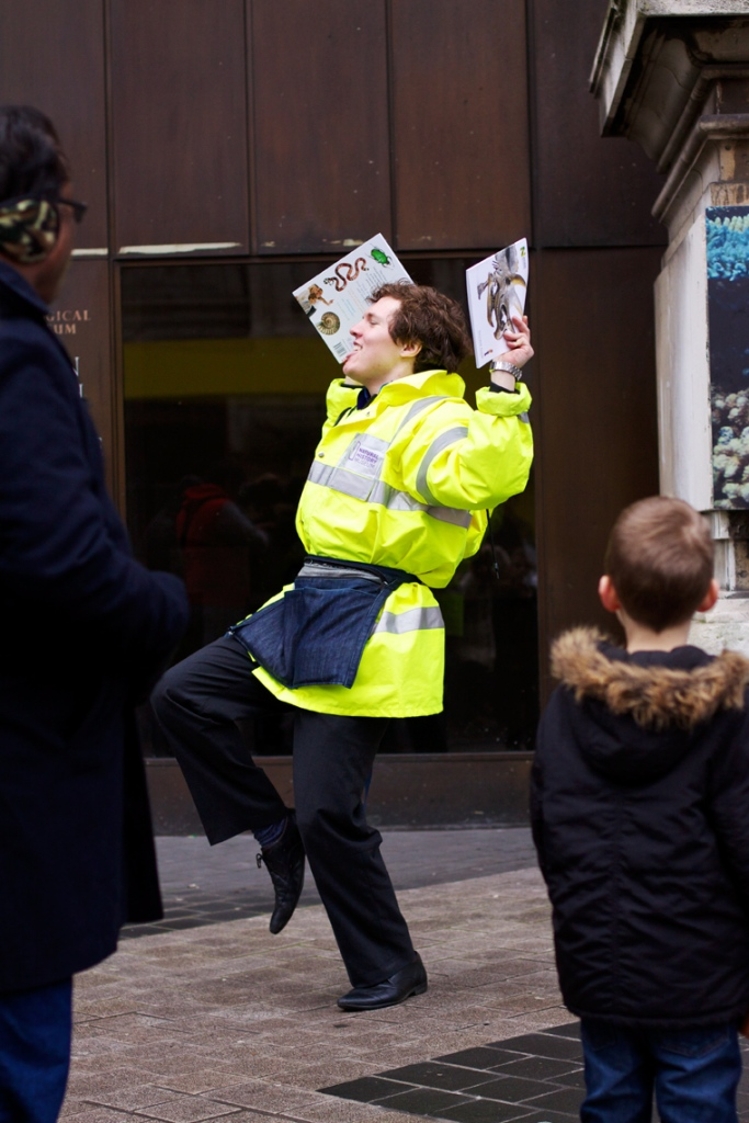 Man in high vis jacket dancing about in a queue outside the Natural History and Science Museum in London