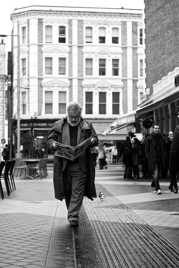 Man walking along street reading a newspaper