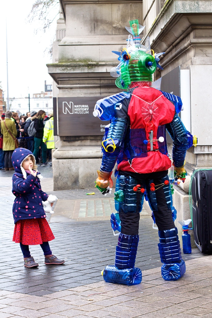 Girl looks up at a man dressed in plastic bottles