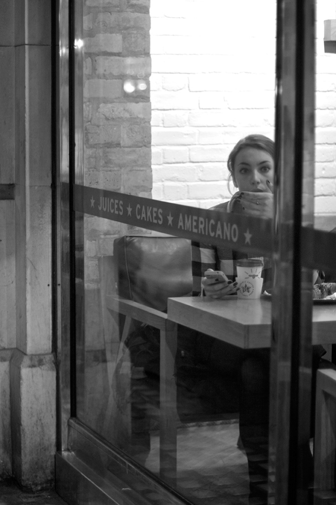 Woman looks out of a  cafe window in Soho