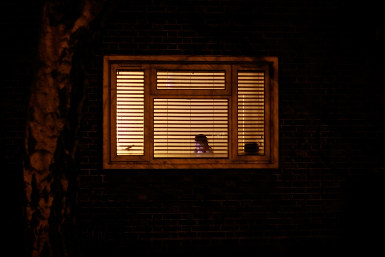 Woman at a window with venetian blinds