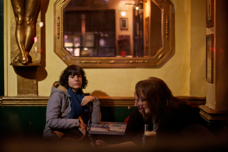 A woman in a pub looking over at 2 other women who are looking at a smartphone