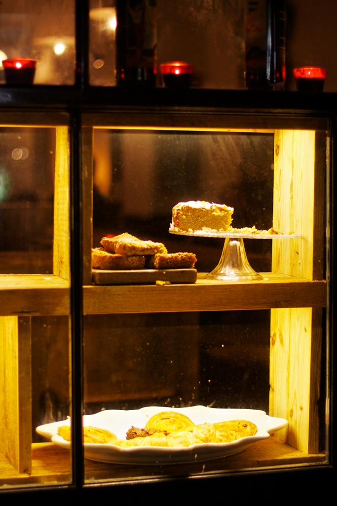 Cakes in a cafe window in yellow light