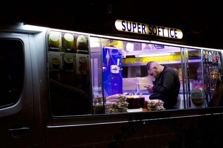Man in ice cream van looking at his phone