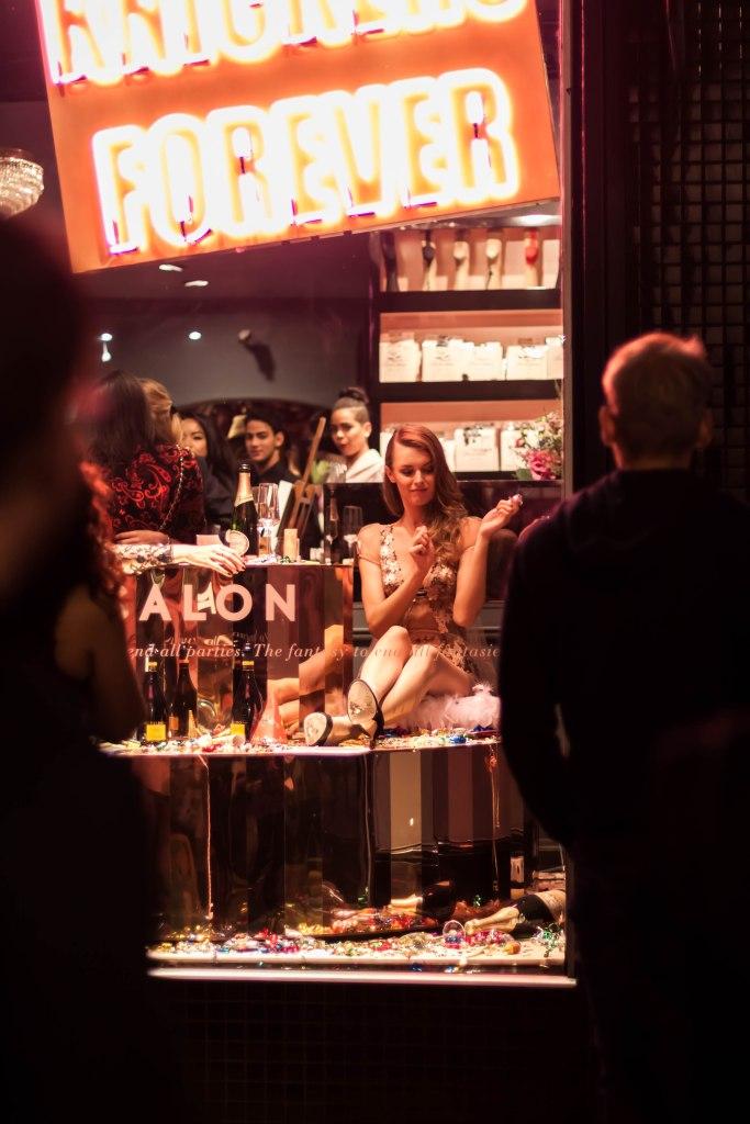 People look at model posing in window