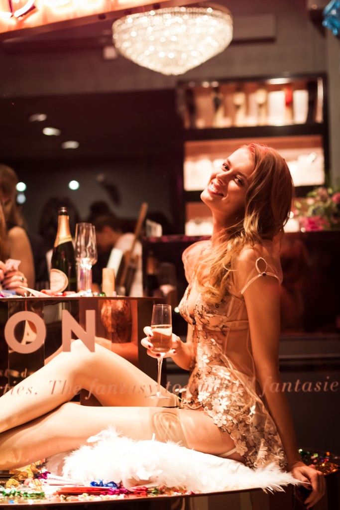 Model poses in underwear in shop window at night
