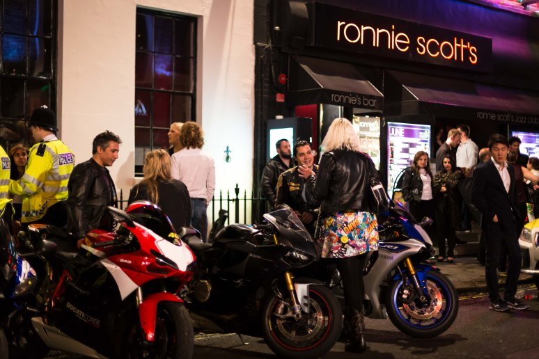 A man on a motorbike chats to a woman outside Ronnie Scotts in Soho, London