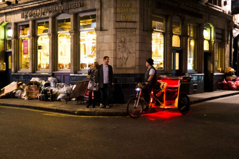 A rickshaw driver chats to a couple outside the Intrepid Fox, Soho, London