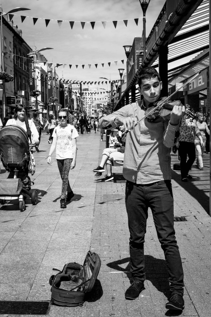 Young man busking, playing the violin in Southend town centre