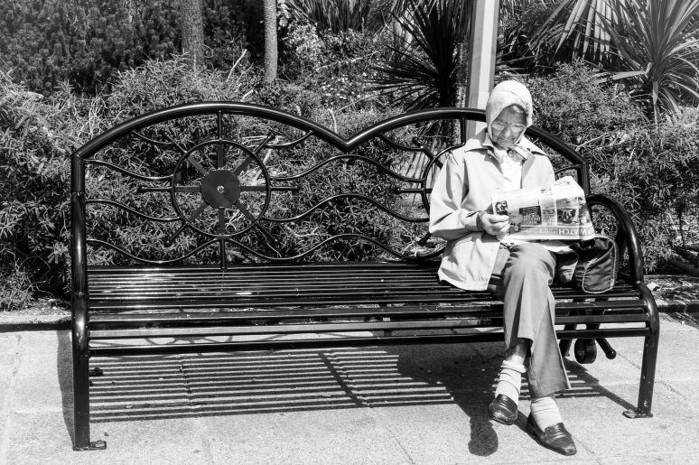Elderly women sitting on a bench reading a newspaper, wearing headscarf and jacket