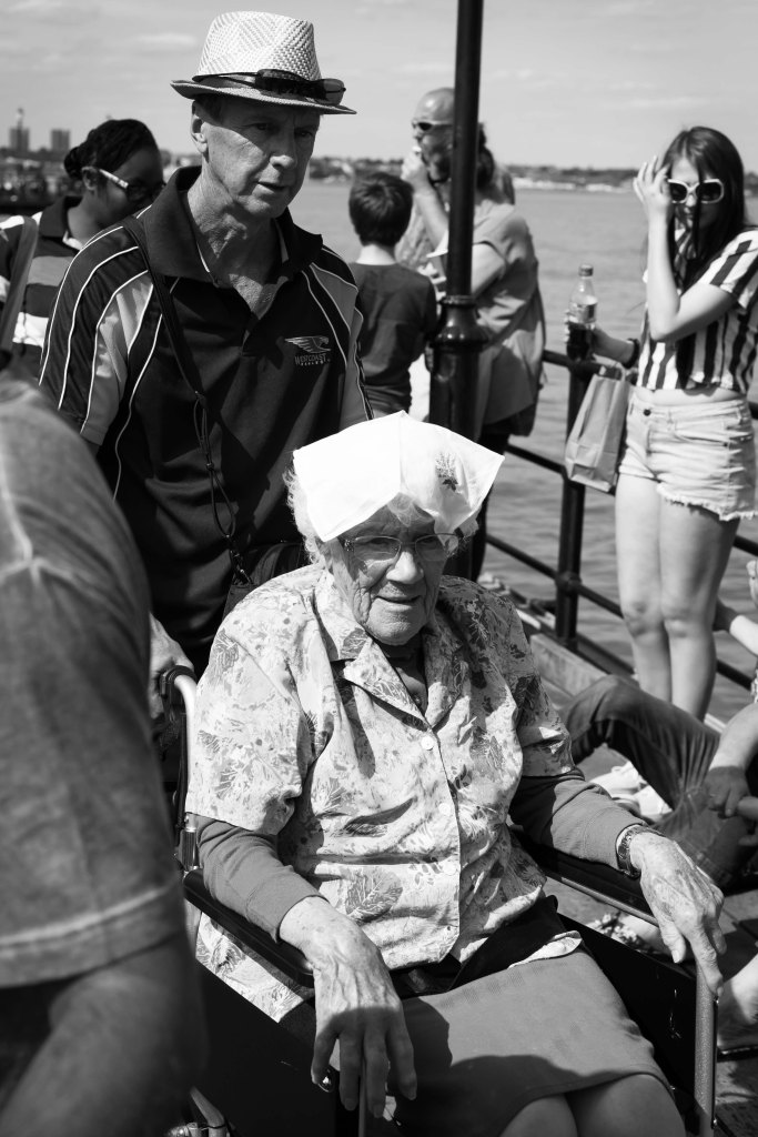 An elderly lady in a wheelchair with a handkerchief on her head on Southend Pier