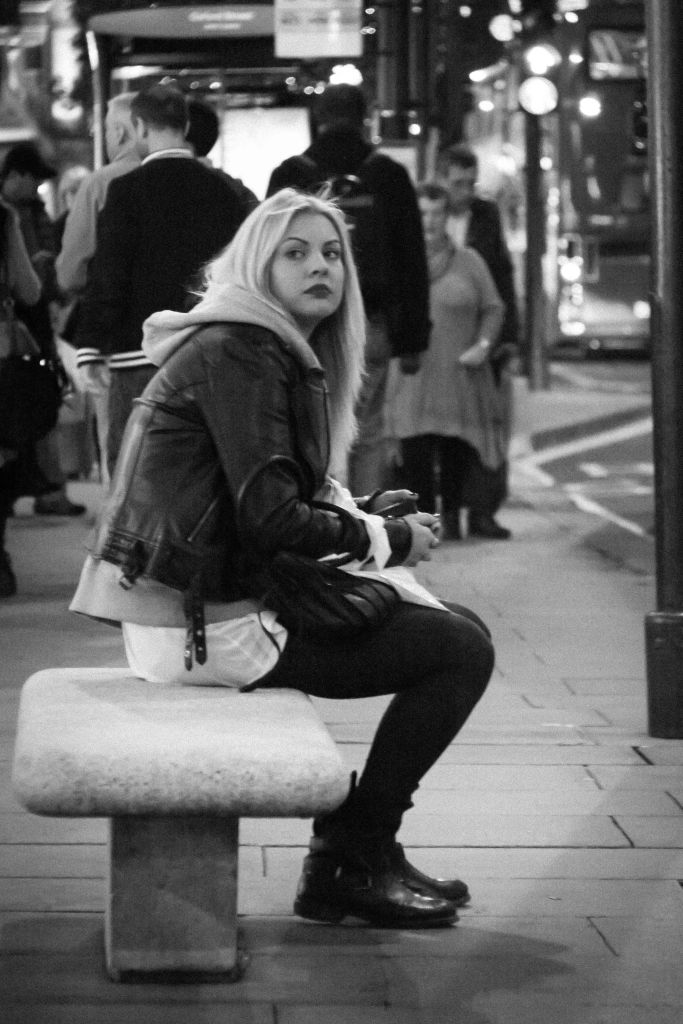 Woman sitting waiting for a bus in Oxford Street, London