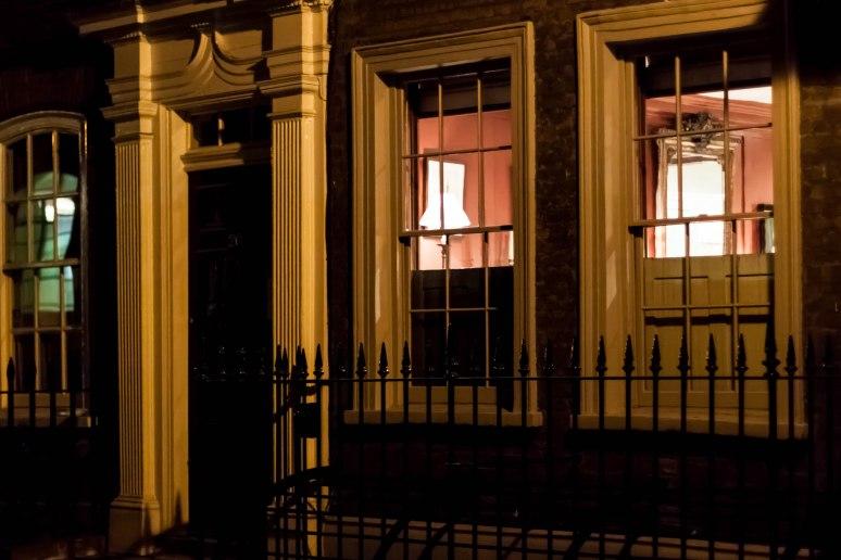 Looking over shutters into lit windows in Spitalfields, London